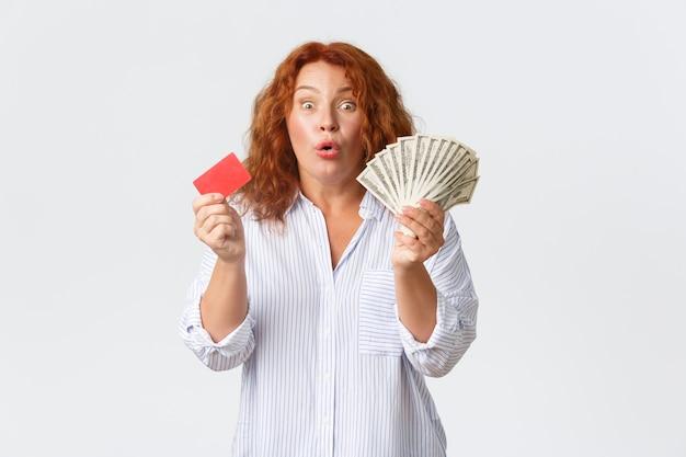Koncepcja pieniądze, finanse i ludzie. wesoła i podekscytowana ruda kobieta w średnim wieku w swobodnej bluzce, trzymająca pieniądze i kartę kredytową z optymistycznym uśmiechem, stojąca na białej ścianie.