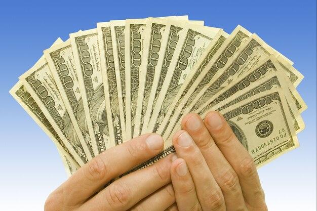 Koncepcja pieniędzy. dolarów w rękach na niebieskim tle