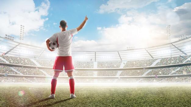 Koncepcja piłki nożnej. piłkarz trzyma piłkę na profesjonalnym stadionie i rozmawia z fanami.