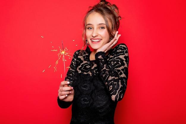Koncepcja pirotechniki i ludzi - uśmiechnięta młoda kobieta lub nastolatka szczęśliwa kobieta z zimnymi ogniami świętować w czarnej sukience na czerwonym tle. dziewczyna jest zaskoczona