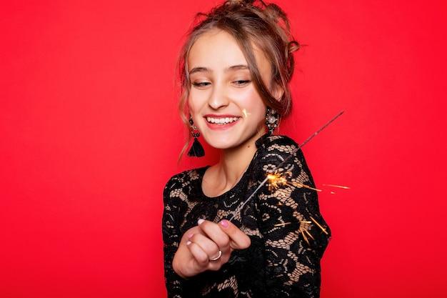Koncepcja pirotechniki i ludzi - uśmiechnięta młoda kobieta lub nastolatka szczęśliwa kobieta z zimnymi ogniami świętować w czarnej sukience na czerwonym tle. dziewczyna patrząca na ogień, zaskoczona