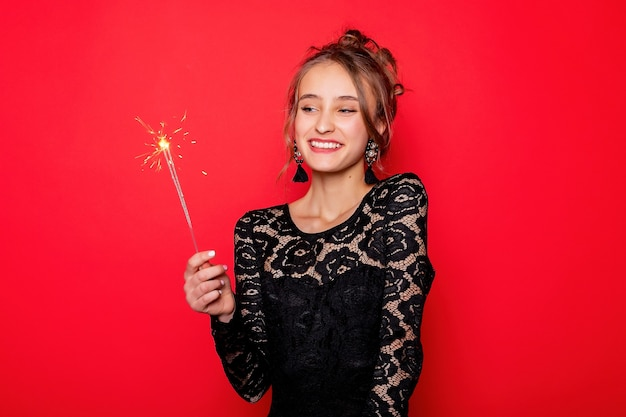 Koncepcja pirotechniki i ludzi - uśmiechnięta młoda kobieta lub nastolatka szczęśliwa kobieta z zimnymi ogniami świętować w czarnej sukience na czerwonym tle. dziewczyna patrząca na ogień