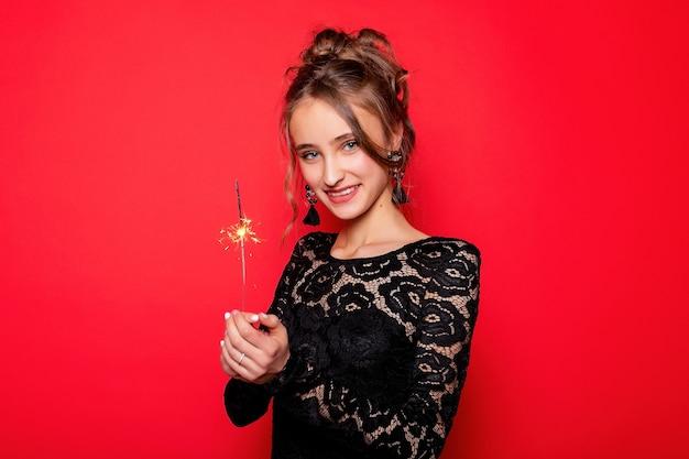 Koncepcja pirotechniki i ludzi - uśmiechnięta młoda kobieta lub nastolatka szczęśliwa kobieta z zimnymi ogniami świętować w czarnej sukience na czerwonym tle. dziewczyna uśmiecha się do kamery