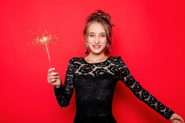 Koncepcja pirotechniki i ludzi - uśmiechnięta młoda kobieta lub nastolatka szczęśliwa kobieta z zimnymi ogniami świętować w czarnej sukience na czerwonym tle.