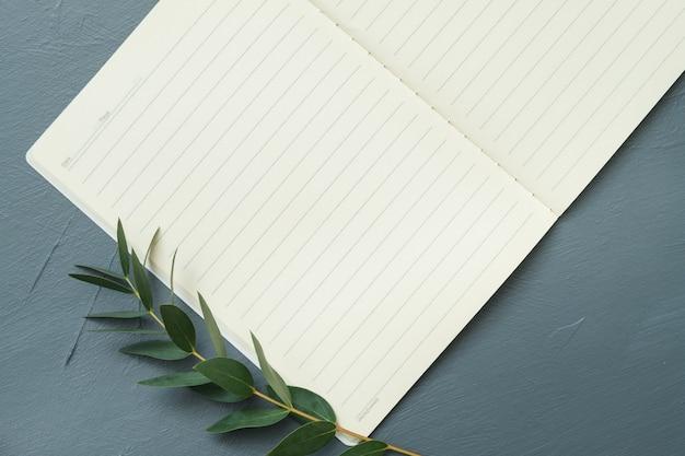 Koncepcja pisania przepisu. puste strony notesu i gałązka oliwna na szarym tle. leżał na płasko.
