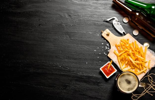 Koncepcja piwa. piwo i frytki z sosem pomidorowym na tablicy. wolne miejsce na tekst. widok z góry
