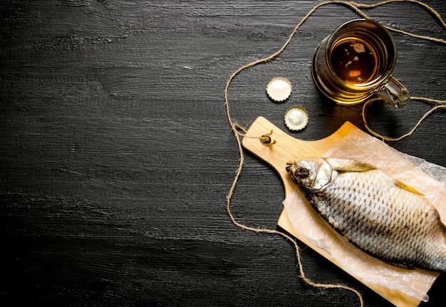 Koncepcja piwa. suszone ryby i świeże piwo na tablicy szkolnej