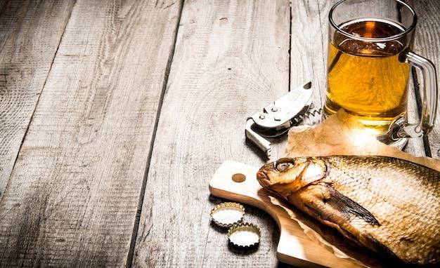 Koncepcja piwa wędzona ryba i świeże piwo na drewnianym stole