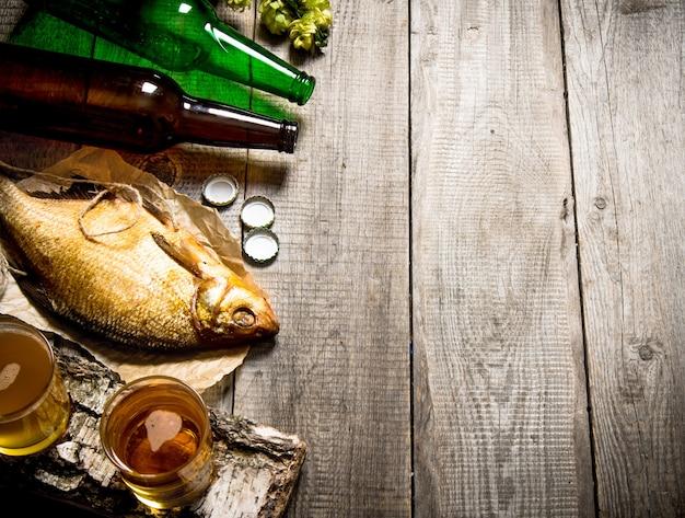 Koncepcja piwa. wędzona ryba i świeże piwo na drewnianym stole.