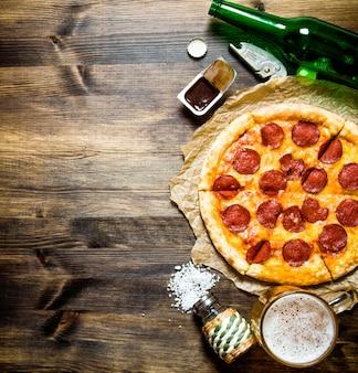 Koncepcja pizzy z piwem pizza pepperoni z piwem na drewnianym stole