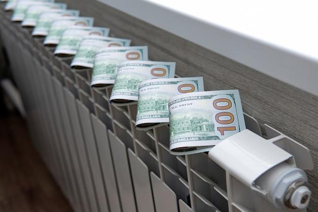 Koncepcja płacenia za ogrzewanie w domach o zimnym klimacie. pieniądze w gotówce leżą na białym metalowym kaloryferze w pobliżu okna.