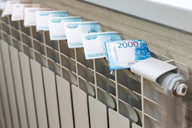 Koncepcja płacenia za ogrzewanie w domach o zimnym klimacie. zbliżenie banknotów dolarowych na grzejniku