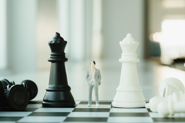 Koncepcja planowania biznesowego. mała biznesmen postać stoi i chodzi na szachownicy z szachowymi kawałkami.