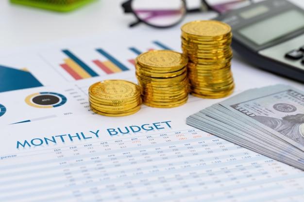 Koncepcja planowania budżetu. wydruk miesięcznego budżetu ze złotą monetą, banknotem i kalkulatorem na biurku.