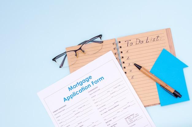 Koncepcja planowania kosztów. otwórz notatnik z napisem to-do-list długopis pieniądze dolary okulary formularz wniosku o kredyt hipoteczny i mały model domu na pastelowym tle, makieta, widok z góry, układanie na płasko, miejsce na kopię