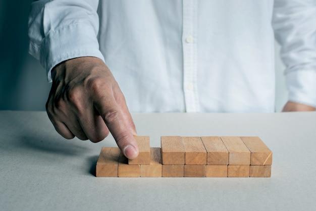 Koncepcja planu i strategia w biznesie z blokiem drewna. mężczyzna ma umieścić drewniany blok na stole. sukces rozwoju koncepcji biznesowej