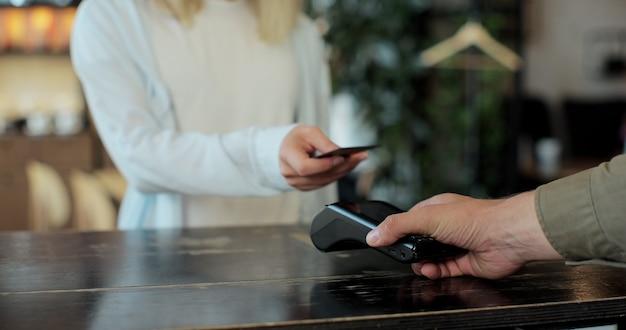 Koncepcja płatności mobilnej - bliska młoda kobieta płaci za pomocą karty kredytowej płatności zbliżeniowych dla jej zamówienia kawy w kawiarni. klient korzysta z telefonu komórkowego, aby zapłacić za pośrednictwem terminala bankowego.