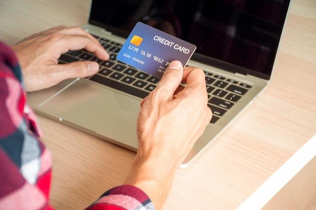 Koncepcja płatności online, ręce młodych mężczyzn korzystających z kart kredytowych i komputerów do zakupów online lub płatności rachunków online.