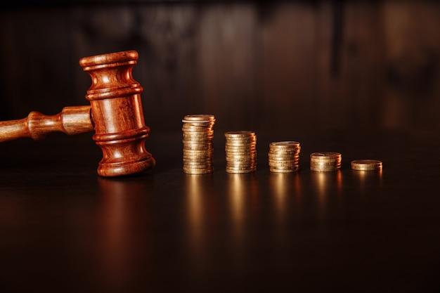 Koncepcja płatności podatku. stos monet z drewnianym młotkiem sędziowskim.