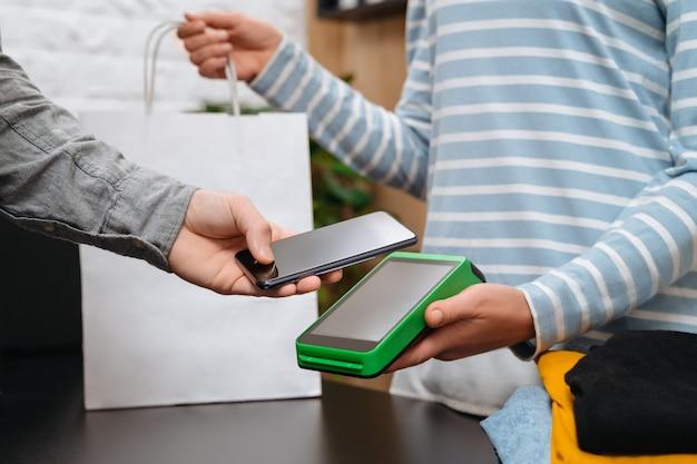 Koncepcja płatności zbliżeniowych, klient płci męskiej posiadający smartfon w pobliżu technologii nfc na ladzie