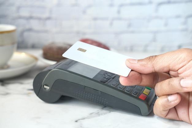 Koncepcja płatności zbliżeniowych z młodym człowiekiem płacącym kartą kredytową