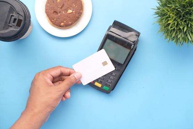 Koncepcja płatności zbliżeniowych z młodym mężczyzną płacącym kartą kredytową