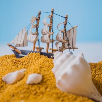 Koncepcja plaży z bliska widok seashelles i żaglówka