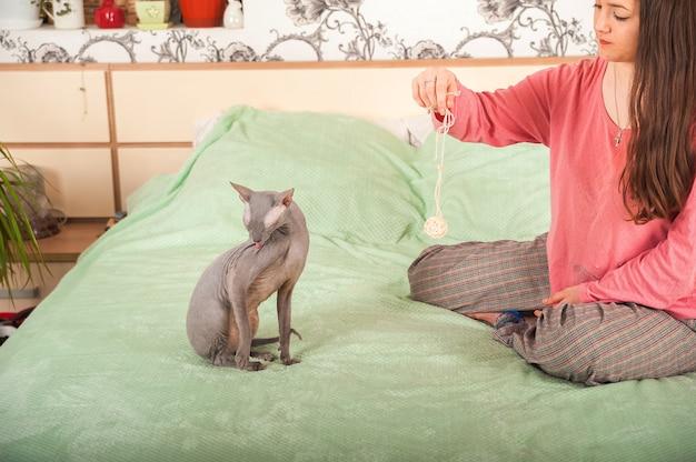 Koncepcja pobytu w domu. dziewczyna z kotem sphinx i scottish fold bawi się na łóżku, przytula.