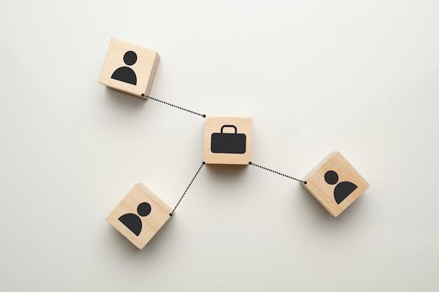 Koncepcja początkowa - abstrakcyjne znaki skrzynki i ludzi na drewnianych kostkach z białą przestrzenią.