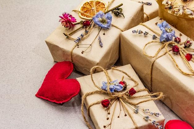 Koncepcja podarunku zero odpadów. ekologiczne opakowanie na walentynki lub urodziny. świąteczne pudełka z papieru rzemieślniczego z różnymi dekoracjami organicznymi.