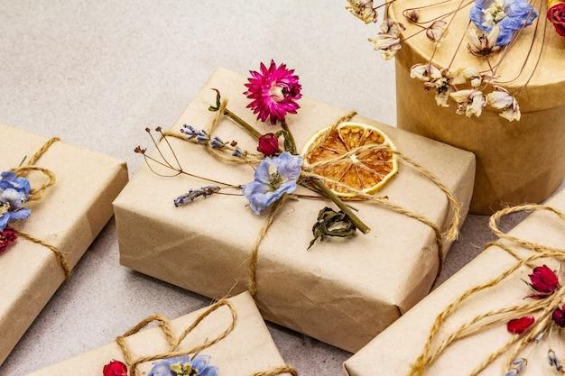 Koncepcja podarunku zero odpadów. urodziny ekologiczne opakowanie. świąteczne pudełka z papieru rzemieślniczego z różnymi dekoracjami organicznymi.