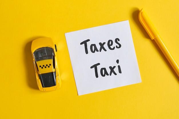 Koncepcja podatku od taksówek jako napis na naklejce obok samochodzika na żółtej ścianie