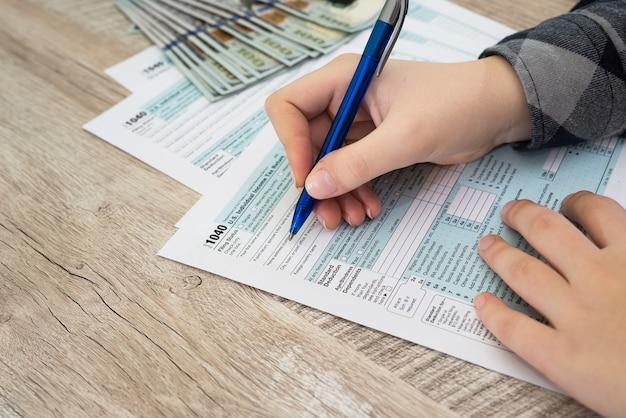 Koncepcja podatku. zamknij ręcznie składanie formularza podatkowego w usa. formularz podatkowy nas koncepcja wypełnienia dłoni biura dochodów