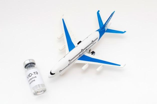 Koncepcja podróżowania podczas pandemii covid-19. fiolka ze szczepionką przeciwko koronawirusowi i model samolotu.