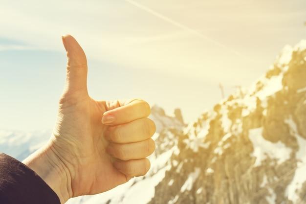 Koncepcja podróży. dokonywanie thumb up na tle przyrody. góry w tle rozmycie. piękne tło nieba.