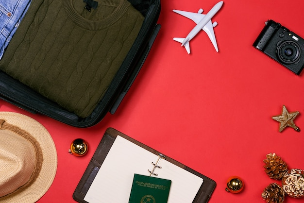 Koncepcja podróży holiday - paszport, aparat fotograficzny, czapka, samolot, ozdoby świąteczne na czerwonym tle
