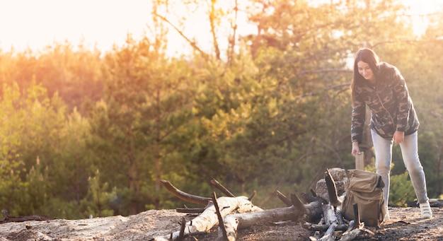 Koncepcja podróży i aktywnego stylu życia. młoda kobieta podróżnik z plecakiem w lesie przy zmierzchem