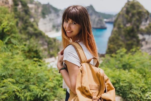 Koncepcja podróży i przygody. szczęśliwa kobieta z plecakiem podróżująca po indonezji na wyspie nusa penida.