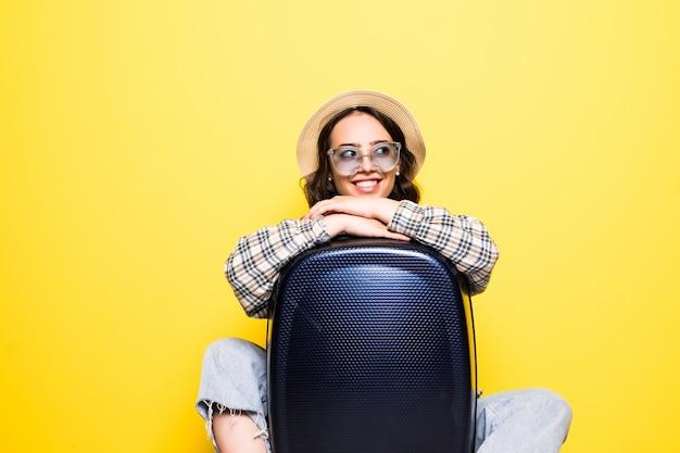 Koncepcja podróży i stylu życia. portret dziewczynki w słomkowym kapeluszu i okularach przeciwsłonecznych z walizką patrząc na białym tle
