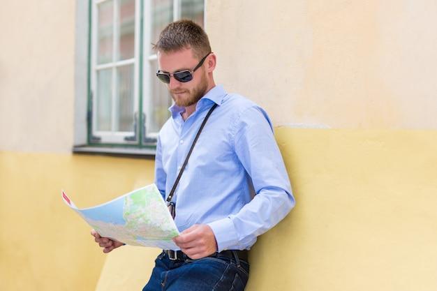 Koncepcja podróży i turystyki - młody człowiek turysta patrząc na mapę miasta