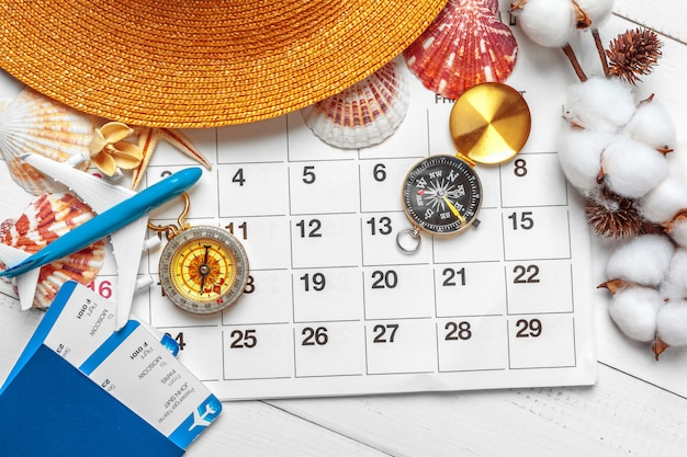 Koncepcja podróży i wakacji, kompas w kalendarzu planowania