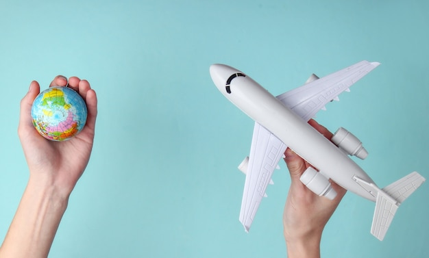 Koncepcja podróży. kobiece ręce trzymając kulę ziemską i figurkę samolotu pasażerskiego na niebieskim tle