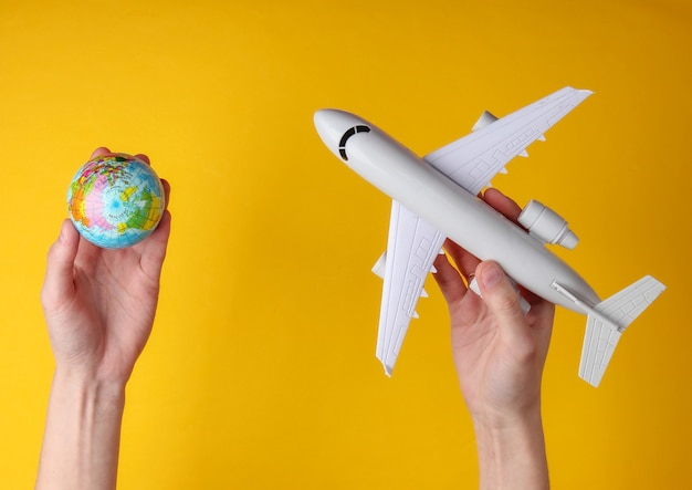 Koncepcja podróży. kobiece ręce trzymając kulę ziemską i figurkę samolotu pasażerskiego na żółtym tle