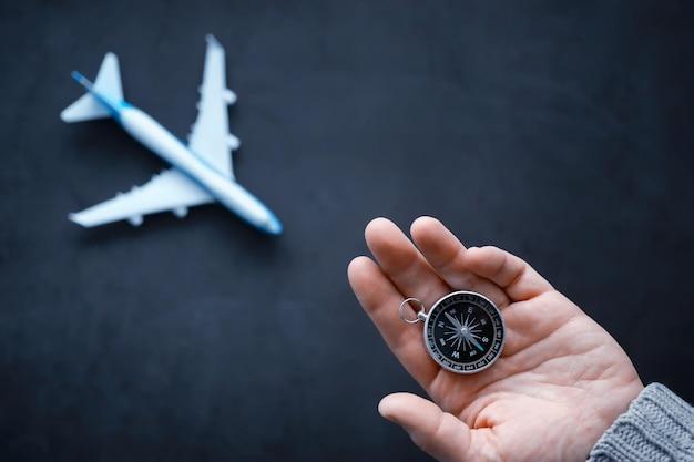 Koncepcja podróży. kompas magnetyczny w dłoni. retro nawigator w ręku tło mapy i samolotu. tło przygody.