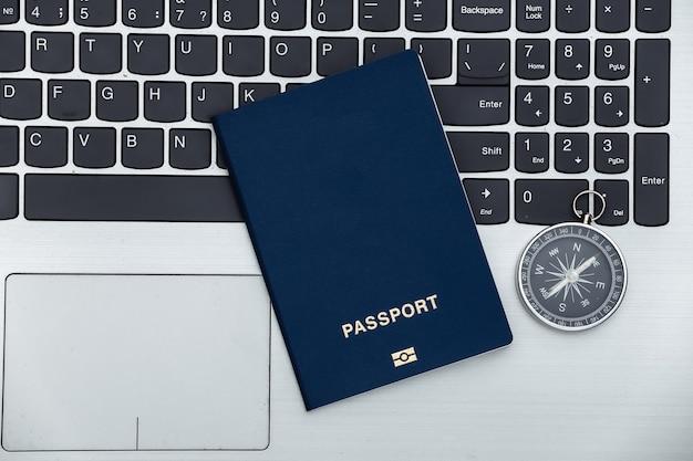 Koncepcja podróży. kompas z paszportem na klawiaturze laptopa