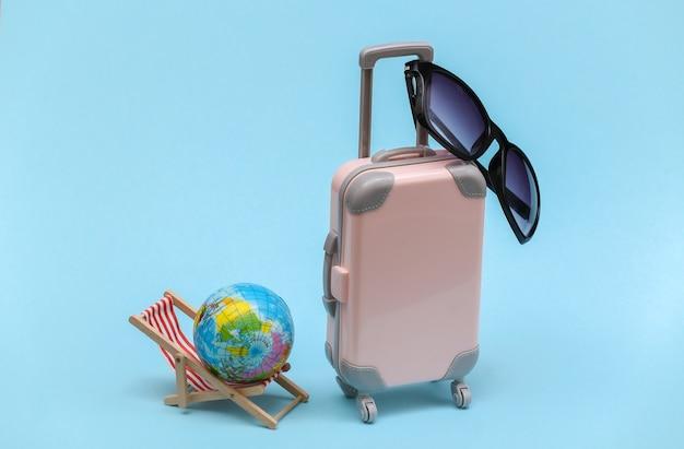 Koncepcja podróży lub plaży. mini walizka podróżna i krzesło z kulą ziemską, okulary przeciwsłoneczne na niebieskim tle. minimalistyczny styl