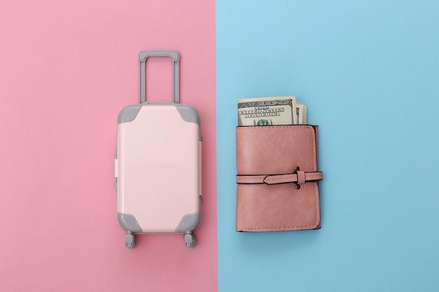 Koncepcja podróży. mini walizka podróżna z tworzywa sztucznego i torebka na różowym niebieskim tle pastelowych. minimalistyczny styl. widok z góry, układ płaski