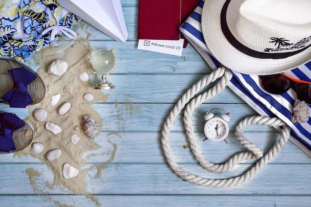Koncepcja podróży pandemicznej koronowirusa letnie akcesoria do wakacji na plaży na niebieskim tle drewnianych