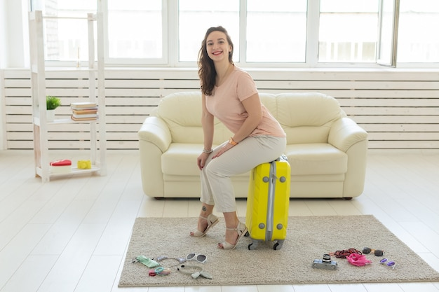 Koncepcja podróży, podróży i wakacji - kobieta z żółtą walizką czeka na taksówkę.