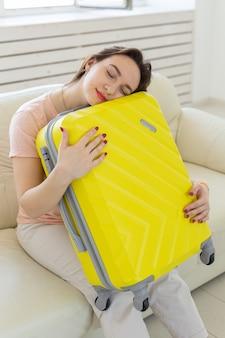 Koncepcja podróży, podróży i wakacji - młoda kobieta ściska swoją żółtą walizkę